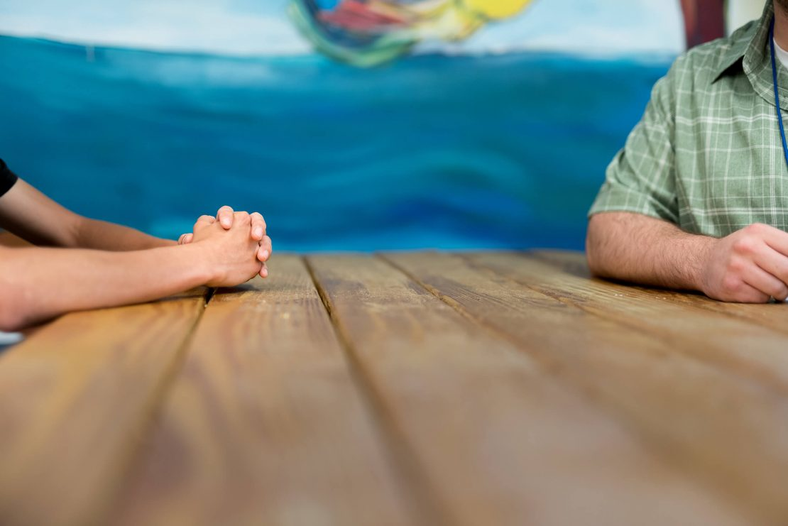 Two people sitting at a table, one with hands crossed