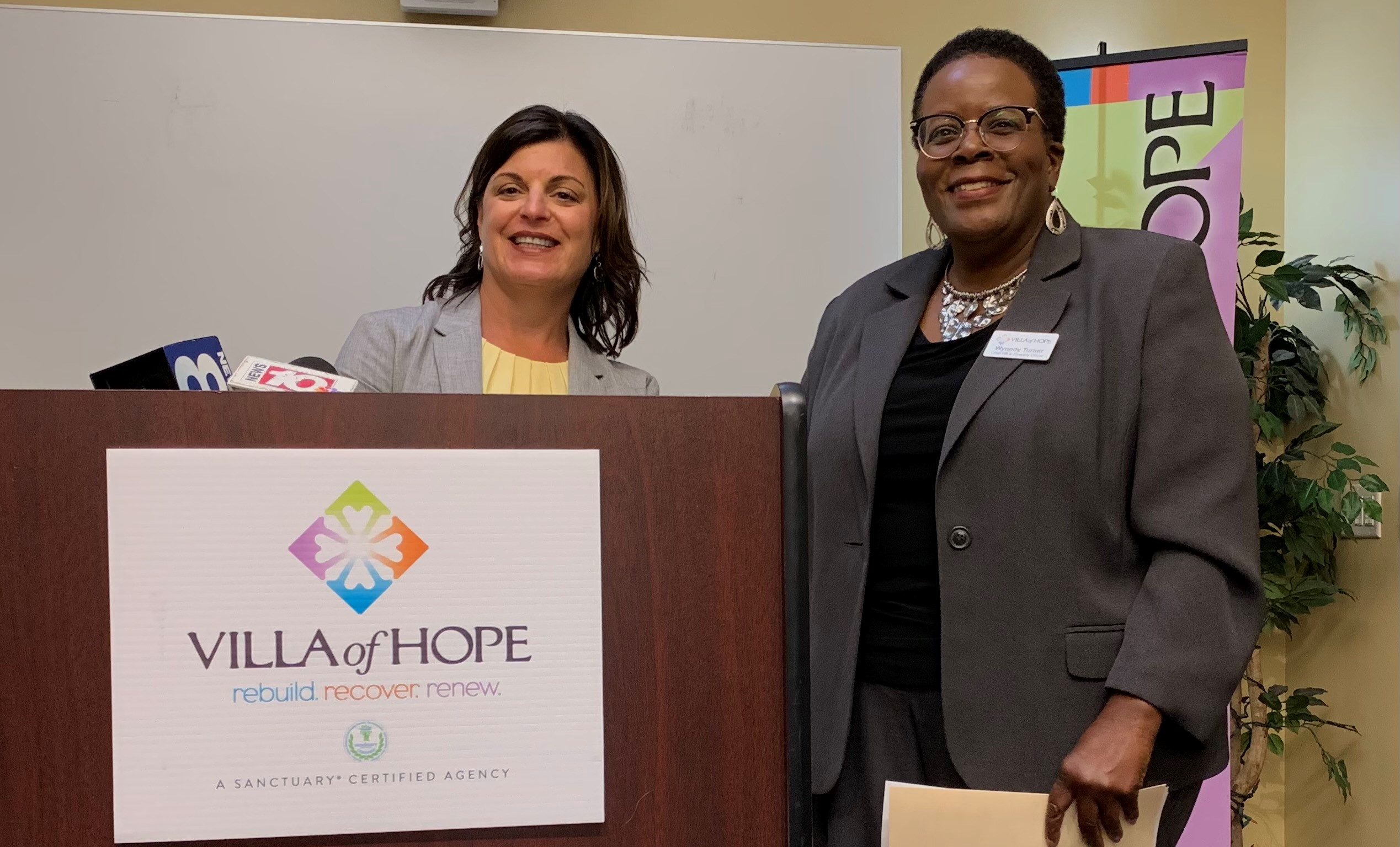 Christina Gullo and Wynndy Turner from Villa of Hope, speaking at a press conference with TV microphones on the podium
